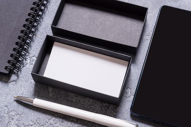 Caixa de papelão preta e cartões de visita brancos na mesa do escritório