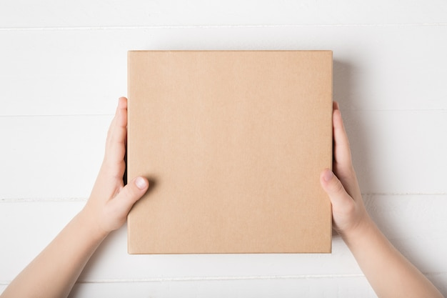 Caixa de papelão quadrada nas mãos de crianças. vista superior, fundo branco