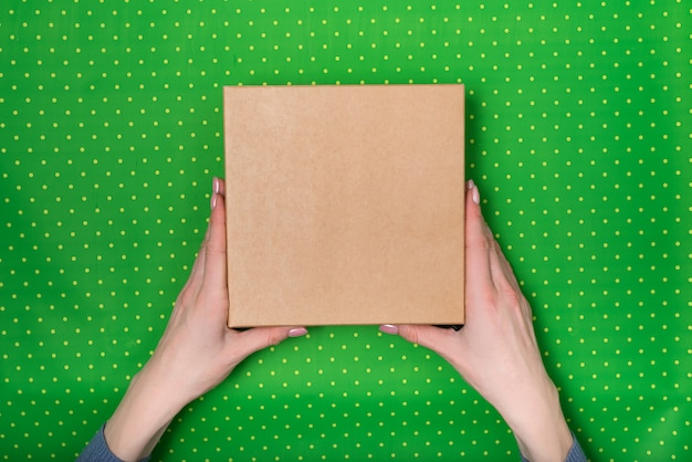 Caixa de papelão quadrada nas mãos femininas. vista superior, fundo verde polka dot