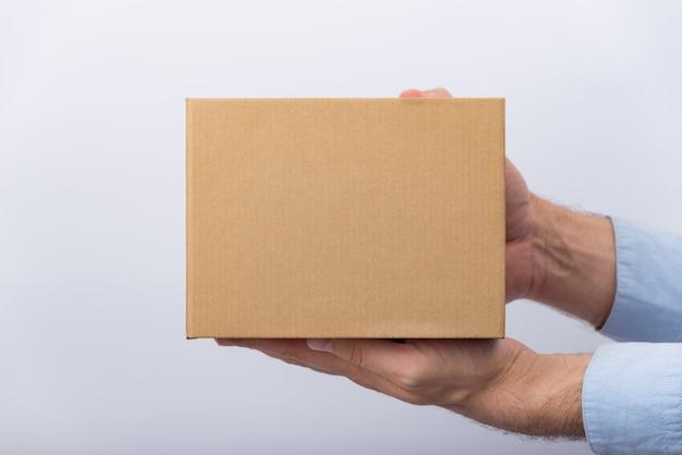 Caixa de papelão quadrada nas mãos masculinas. entrega de encomendas. vista lateral.