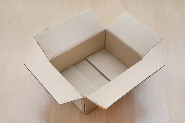 Caixa de papelão retangular aberta vazia na madeira.