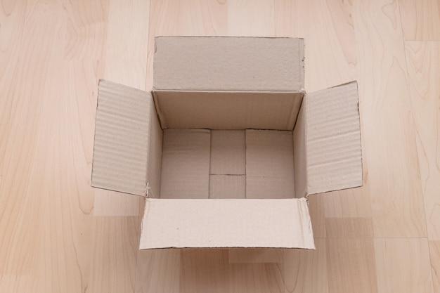 Caixa de papelão retangular aberta vazia na madeira