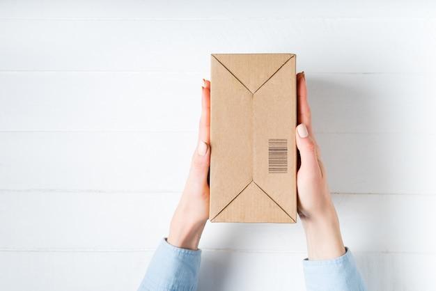 Caixa de papelão retangular com código de barras nas mãos femininas.