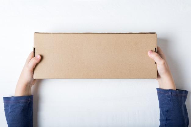 Caixa de papelão retangular nas mãos das crianças.