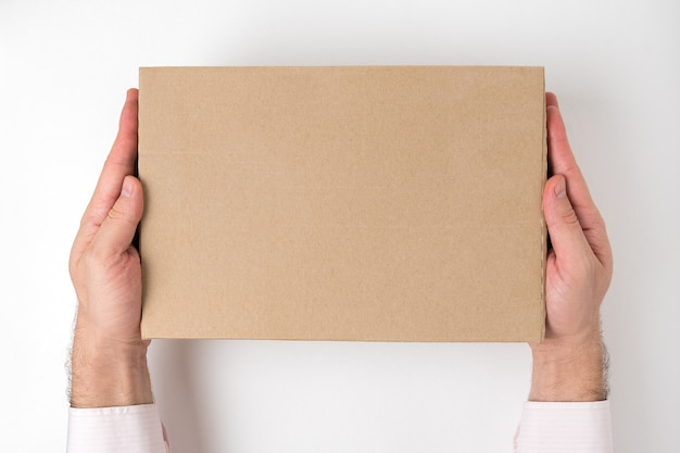 Caixa de papelão retangular nas mãos dos homens. conceito de serviço de entrega. vista do topo