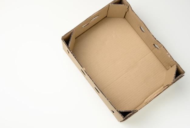 Caixa de papelão retangular vazia de papel pardo sobre fundo branco, caixa sem tampa para legumes e frutas com furos, vista de cima