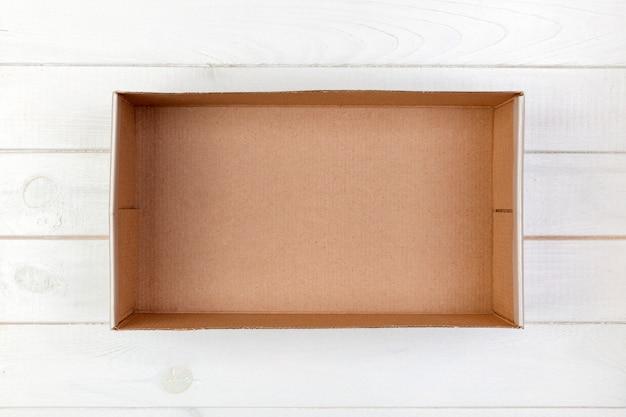 Caixa de papelão vazia em uma vista superior do plano de fundo branco de madeira