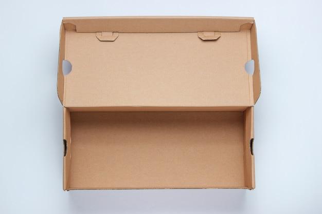 Caixa de papelão vazia na superfície cinza.