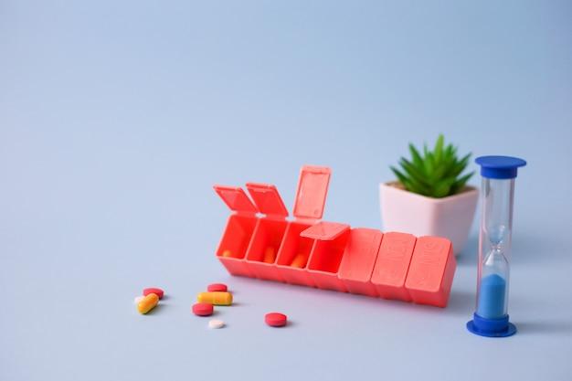 Caixa de pílula rosa de sete dias cheia de medicação ao lado da ampulheta em fundo azul