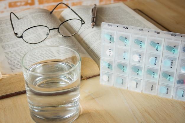 Caixa de pílulas por semana e separar o tempo com medicina e livro na mesa