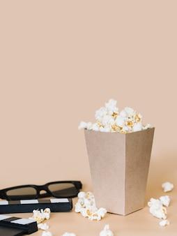 Caixa de pipoca close-up com óculos 3d em cima da mesa