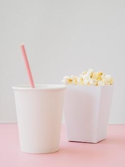 Caixa de pipoca saborosa com bebidas na mesa