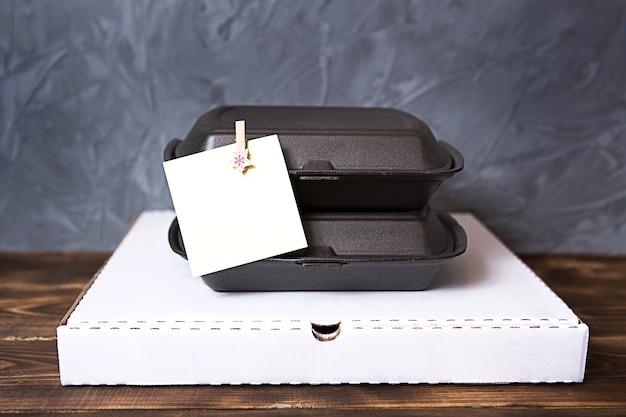 Caixa de pizza com recipientes de comida para entrega