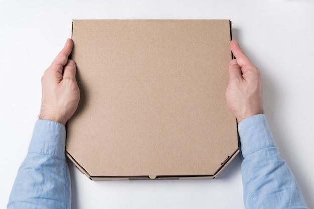 Caixa de pizza nas mãos masculinas. conceito de entrega de comida para casa.