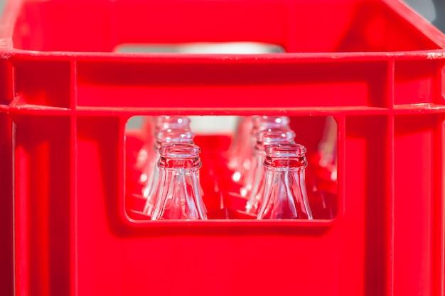 Caixa de plástico vermelha com garrafas de vidro vazias. foto filtrada horizontal
