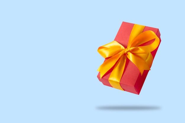 Caixa de presente a voar sobre uma superfície azul clara. conceito de férias, presente, venda, casamento e aniversário.