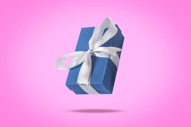Caixa de presente a voar sobre uma superfície rosa clara. conceito de férias, presente, venda, casamento e aniversário.