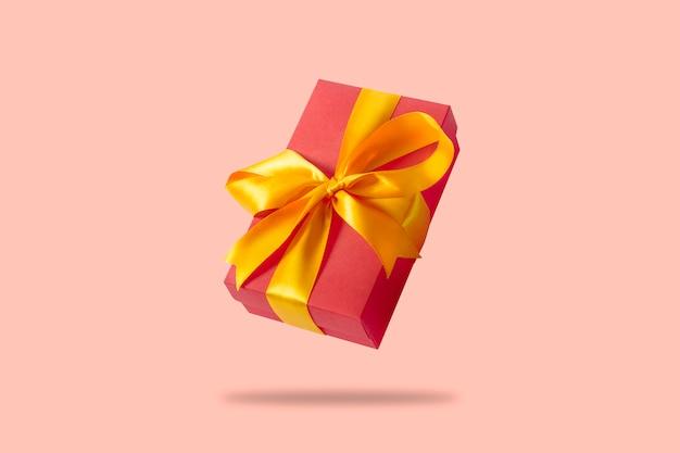 Caixa de presente a voar sobre uma superfície rosa clara.