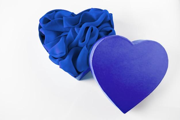 Caixa de presente aberta em forma de coração azul no branco