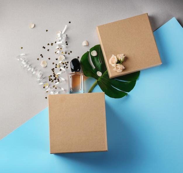 Caixa de presente aberta, perfume e decoração na cor de fundo, vista superior