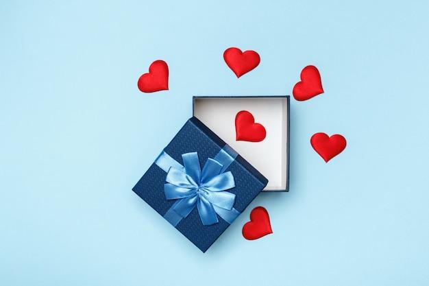 Caixa de presente aberto com corações em fundo azul