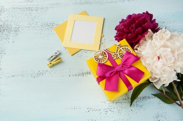 Caixa de presente amarela com arco e peônias