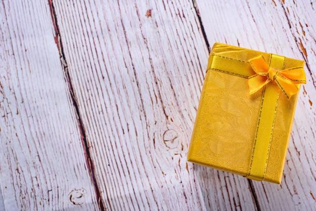 Caixa de presente amarela com fita de arco na mesa de madeira branca, aniversário, conceito de dia de natal. aceitar presentes conceito