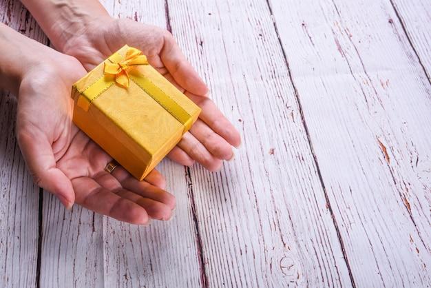 Caixa de presente amarela com fita de arco nas mãos da mulher na mesa de madeira branca, aniversário, conceito de dia de natal. aceitar presentes conceito