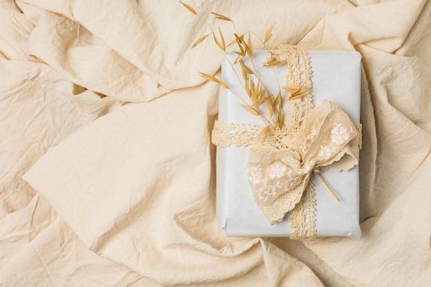 Caixa de presente amarrada com laço de designer sobre folha de cama vincada