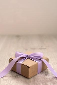 Caixa de presente amarrada com uma fita roxa de cetim.