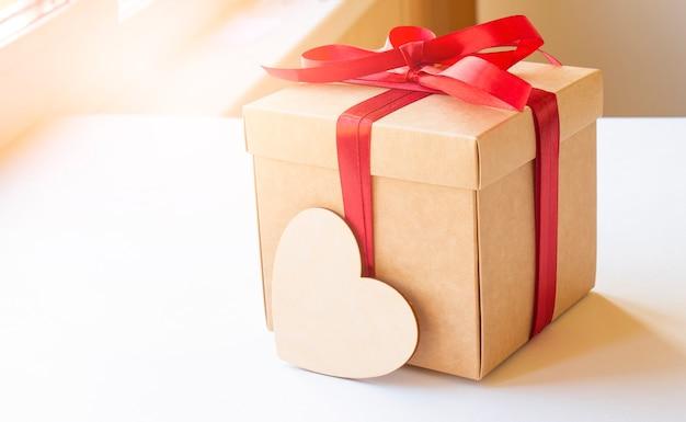Caixa de presente artesanal com coração de madeira em fundo branco