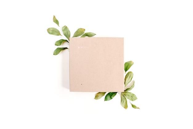 Caixa de presente artesanal e composição floral com folhas verdes
