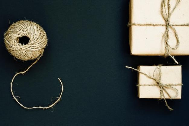 Caixa de presente artesanal embrulhada em papel ofício com coração de madeira vermelho, corda e arco em fundo preto. vista superior, plana