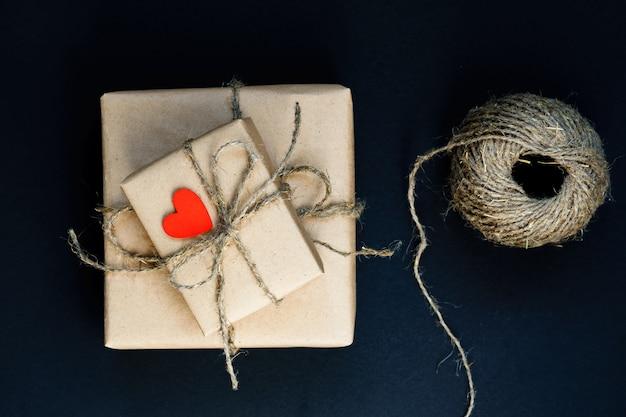 Caixa de presente artesanal embrulhada em papel ofício com coração de madeira vermelho, corda e arco em preto