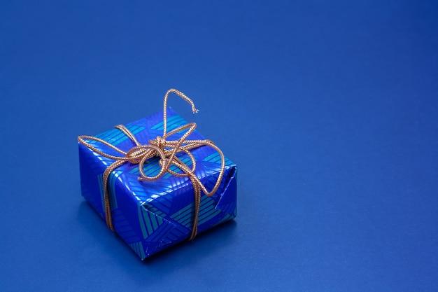 Caixa de presente azul amarrada com uma corda laranja em um fundo azul. copie o espaço.