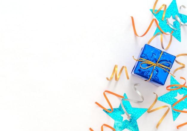 Caixa de presente azul clássica embrulhada com fita dourada, fitas de festa brilhantes e estrelas azuis brilhantes