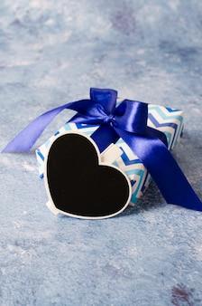 Caixa de presente azul com fita. lousa em forma de coração com espaço de cópia.