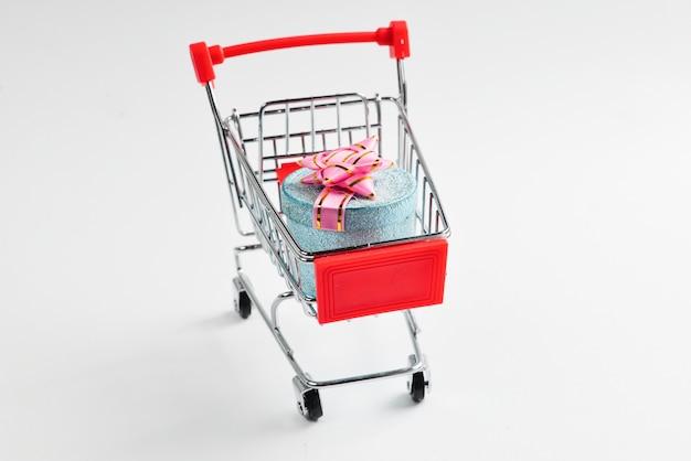 Caixa de presente azul com laço rosa em um carrinho de compras em um branco