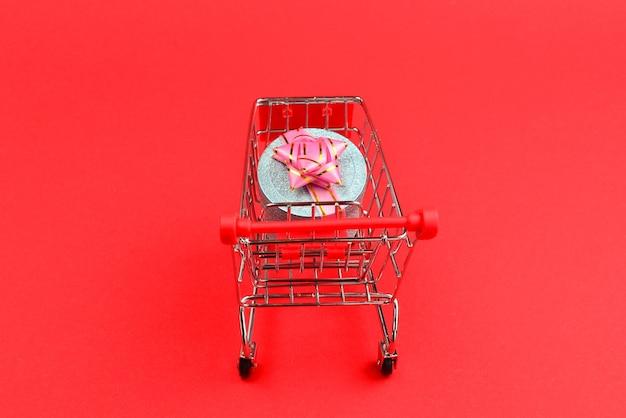 Caixa de presente azul com laço rosa em um carrinho de compras em um fundo vermelho.