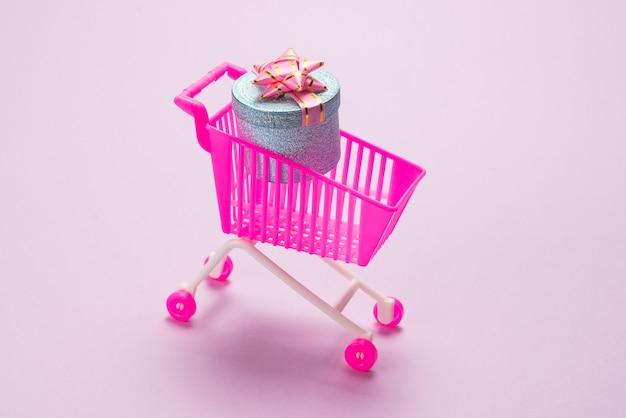 Caixa de presente azul com laço rosa em um carrinho de compras. vista do topo.