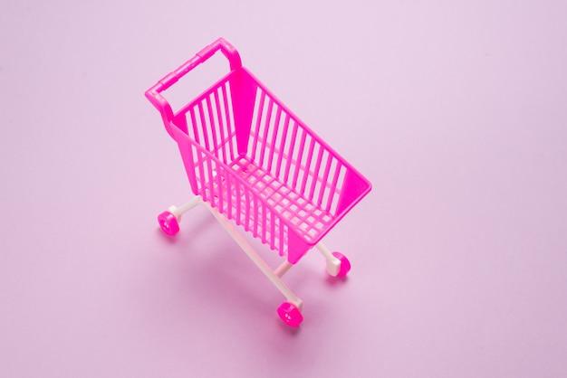Caixa de presente azul com laço rosa em um carrinho de compras