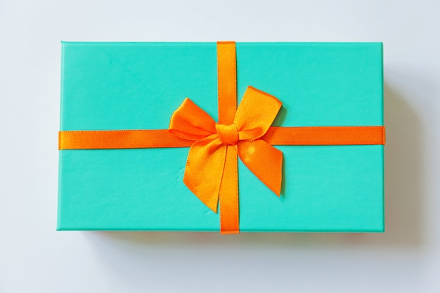 Caixa de presente azul de design minimalista com fita laranja isolada no fundo branco