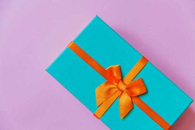 Caixa de presente azul de design minimalista isolada em fundo colorido roxo violeta