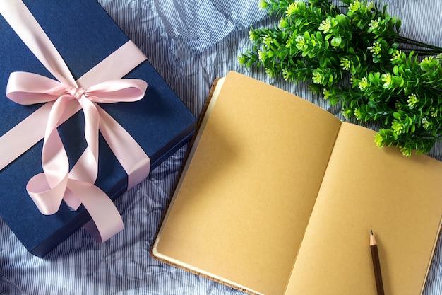 Caixa de presente azul escuro com decoração de fita com livro e flor
