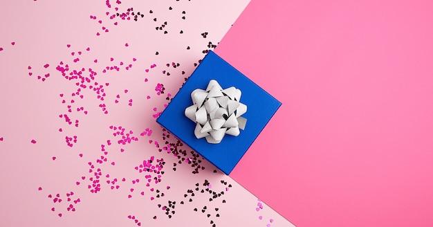Caixa de presente azul quadrado fechado com laço de prata sobre um fundo rosa