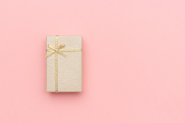 Caixa de presente bege com laço no fundo pastel rosa no estilo minimalista.