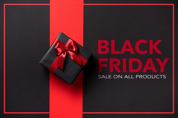 Caixa de presente black friday embrulhada em papel preto com um laço vermelho em um fundo preto com texto.