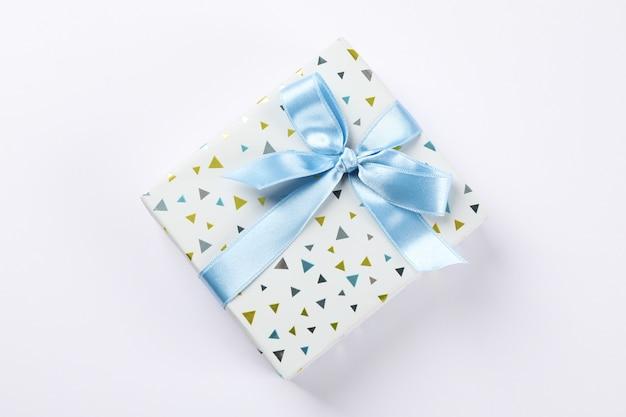 Caixa de presente bonita com laço em fundo branco, espaço para texto