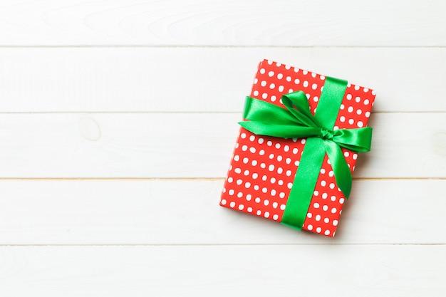 Caixa de presente bonita com um laço colorido em cima da mesa de madeira branca.