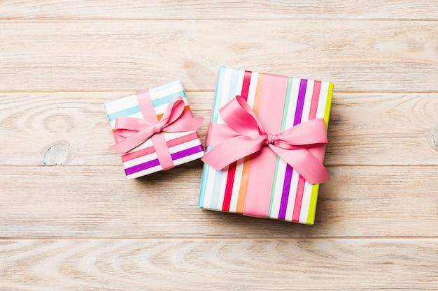 Caixa de presente bonita com um laço colorido na mesa de madeira laranja. vista superior com espaço de cópia para você projetar. conceito de natal